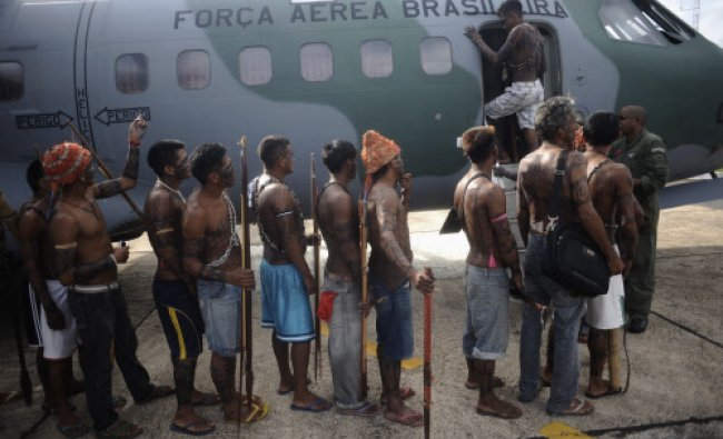 Munduruku Indians, many of who are flying for the first time, board a Brazilian Air Force plane...
