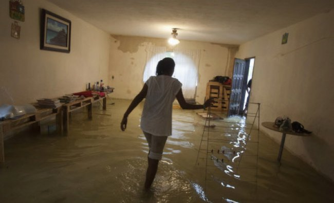 A woman walks inside her flooded home in Mexico\'s resort city Cancun June 4, 2013.