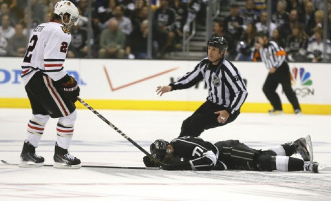 Linesman Brad Kovachik moves in to restrain Chicago Blackhawks\' Duncan Keith (L) after he hit...