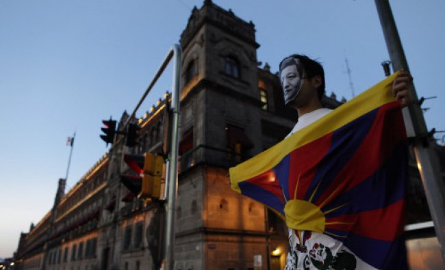 An activist wearing a mask in the image of China\'s President Xi Jinping holds a Tibetan flag...