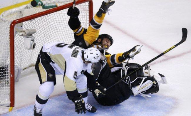 Pittsburgh Penguins\' Deryk Engelland (L) pushes Boston Bruins\' Milan Lucic into Penguins goalie...