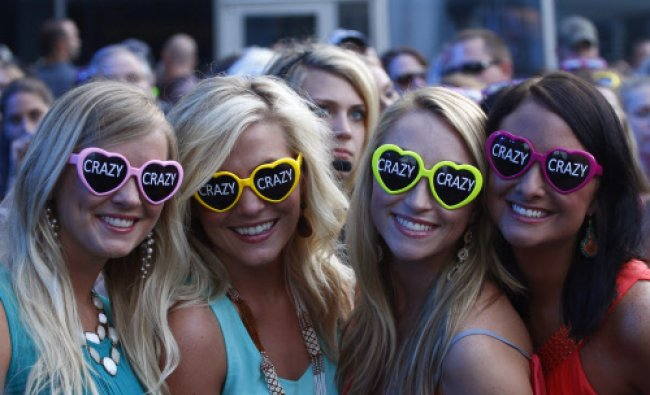 Fans wearing sunglasses promoting Hunter Hayes\' song \'Crazy\' wait for him to perform at the...