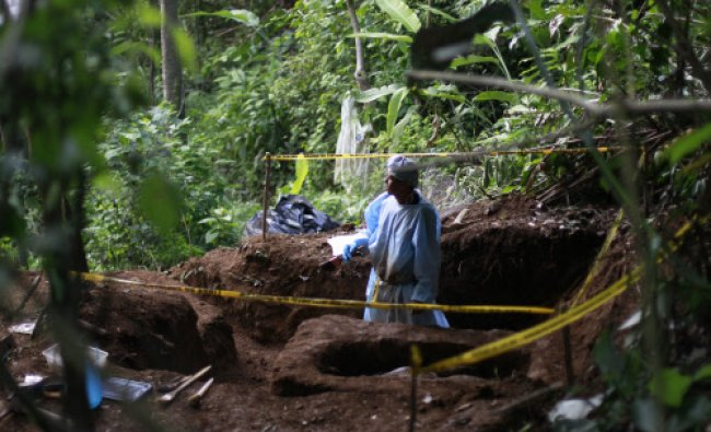 A forensic technician works at a clandestine grave during an exhumation in the mountain range...