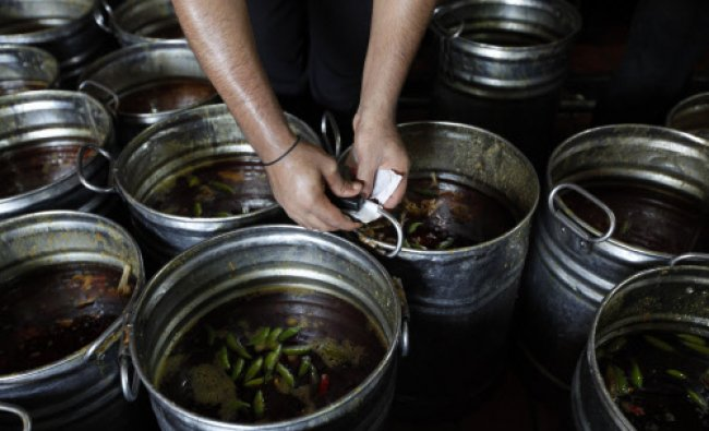 A worker staples a label on a mutton curry pot, before its distribution, in the Saylani Welfare...