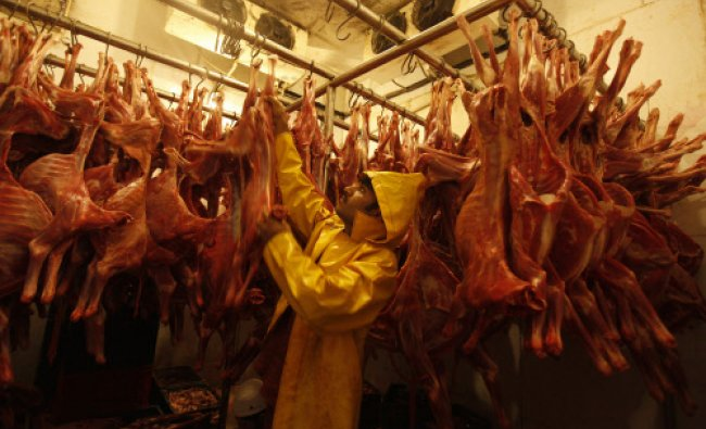 A worker hangs mutton in a cold storage unit in the Saylani Welfare Trust office building in...