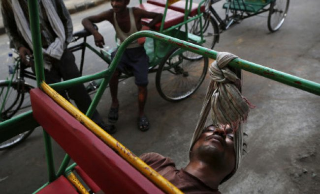 A bicycle rickshaw driver uses a scarf to rest his head while sleeping on his rickshaw in...
