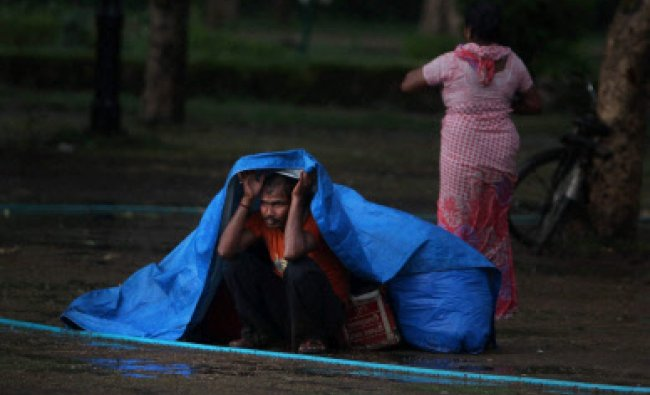 A vendor shields himself with a plastic sheet near India Gate during rains in New Delhi on...