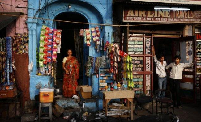 A woman waits for customers in front of her shop in New Delhi, India, Thursday, June 6, 2013...