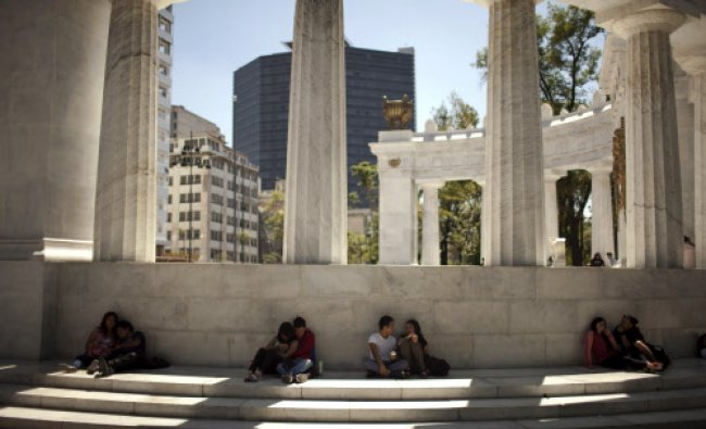 Couples rest in the shade behind the monument in honor of Mexico\'s former President Benito Juarez...
