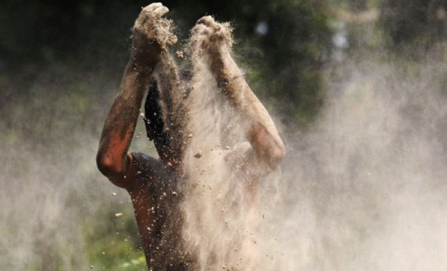 A boy plays with mud on the banks of river Yamuna on a hot day in New Delhi...
