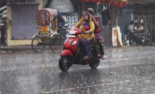 Girls ride scooty on the road during heavy pre monsoon rain in Allahabad on Friday.