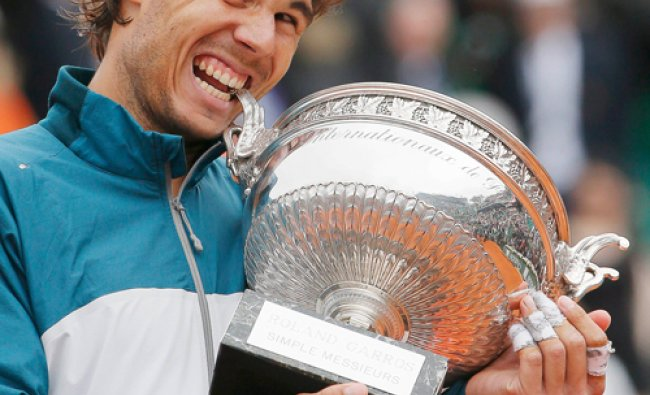 match to win the French Open tennis tournament in Paris Rafael Nadal of Spain bites the trophy...