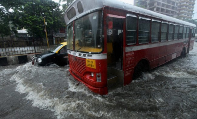 Vehicles wade through a flooded street after heavy downpour in Mumbai on Monday morning...