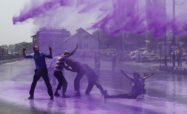 Policemen use colored water from a water cannon to disperse state government workers during a...