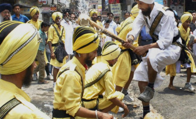 Members of Virasat-E-Khalsa Ghatka Group breaking coconut on their head as they show their skills...