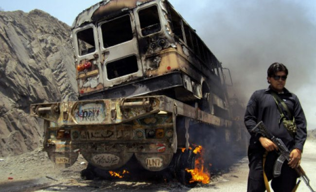 A tribal policeman stands guard near a burning NATO supply convoy in Jamrud...