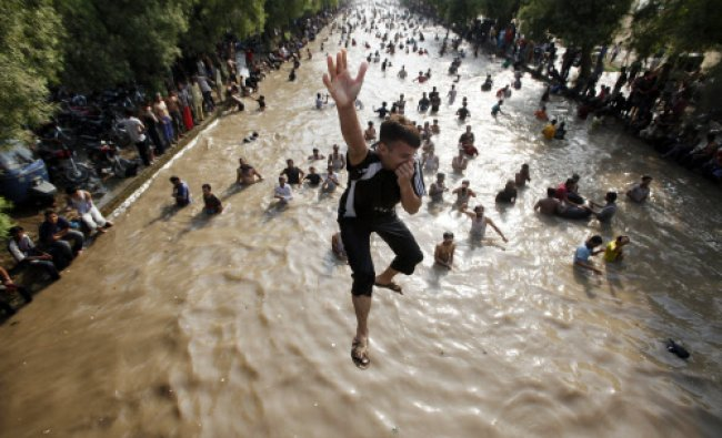A boy jumps into a water canal to cool himself with others on a hot day in Lahore...
