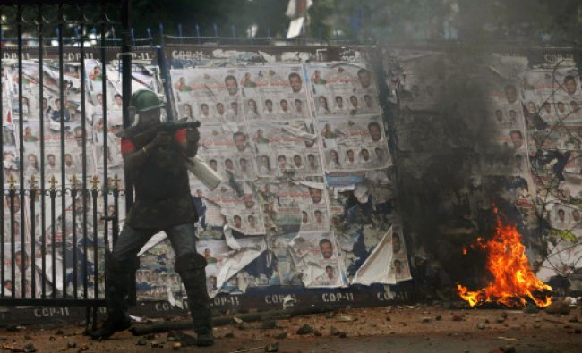A policeman fires tear gas shells at students during a protest demanding creation of a new...