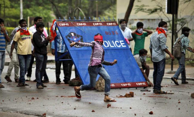 A student protestor hurls stones at policemen during a protest demanding creation of a new...
