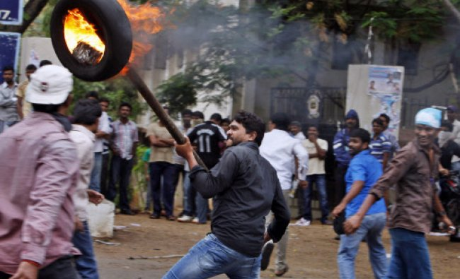 A student holds a burning tire with a rod during a protest demanding creation of a new state...