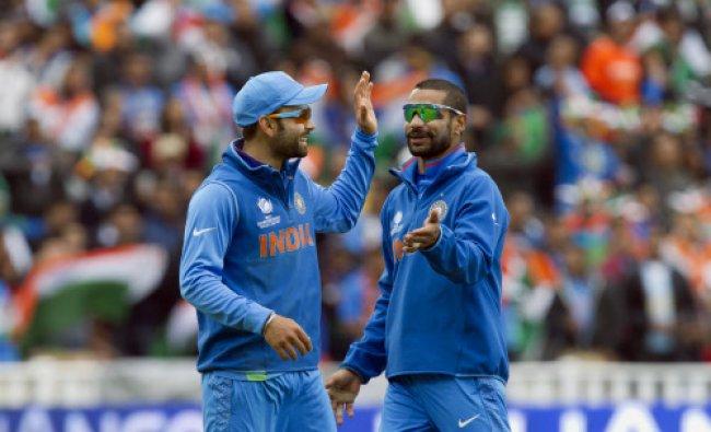 Virat Kohli, left, celebrates with teammate Shikhar Dhawan after running out Pakistan\'s Junaid Khan.