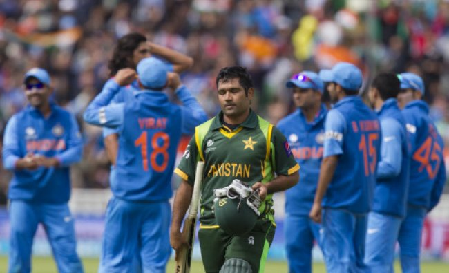 Pakistan\'s Asad Shafiq, centre, walks from the pitch after loosing his wicket for 41 off...