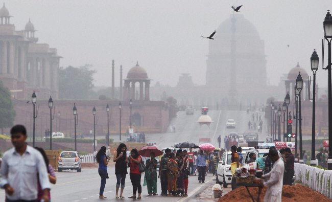 People enjoy at Rajpath during rain in New Delhi on Sunday. PTI Photo