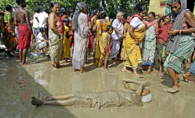 An elderly devotee covered in mud seeks God\'s blessings at an ancient Dharamraj temple in Birbhum...