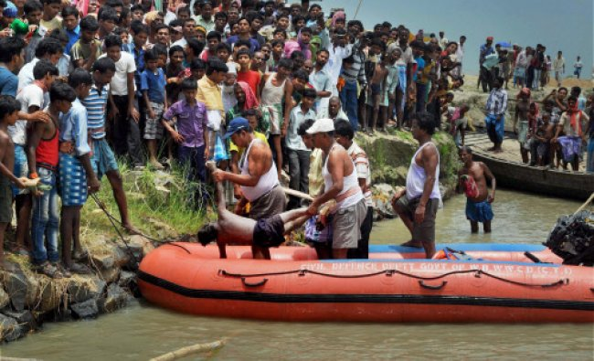Rescuers carry a body recovered from the Ganges river after a ferry boat capsized at Rustampur Ghat