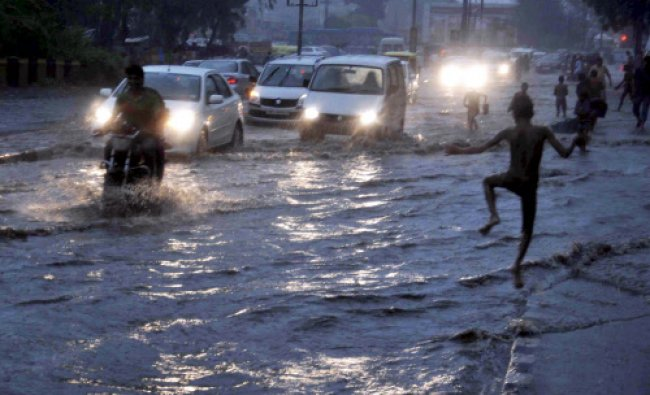 Vehicles move through a water logged road after heavy rain in Faridabad on Sunday.
