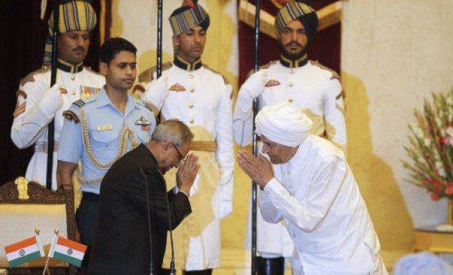 President Pranab Mukherjee (L) greets Sis Ram Ola after administering the oath of union cabinet...