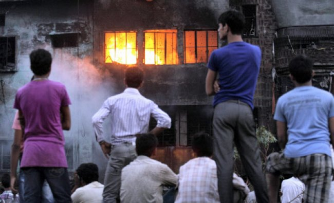 People watch a plastic goods factory in flames at Shahzada Bagh industrial area in New Delhi...
