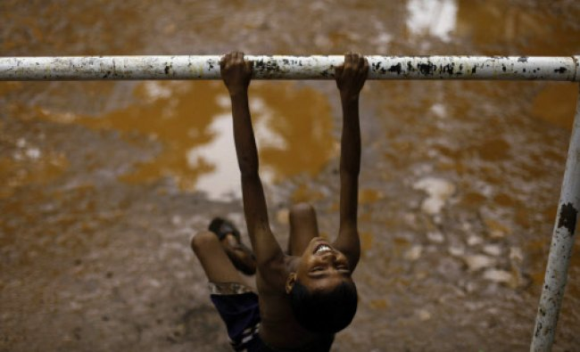 A young Indian boy smiles as he swings in Mumbai, India, Monday, July 17, 2013. AP Photo