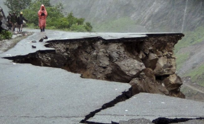 People walk on a road which was caved in after incessant rains on Rishikesh-Mana highway near ...