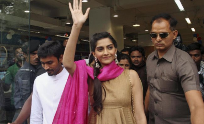 Bollywood actor Sonam Kapoor, center, waves to fans as she leaves a press conference to promote...