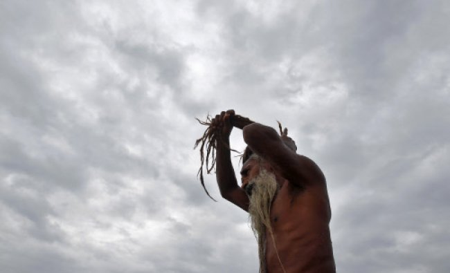 A Sadhu adjusts his hair against the backdrop of monsoon clouds after taking a holy...