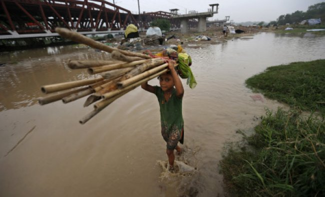 A young girl carries her family belongings to drier grounds as people evacuate the flooded...
