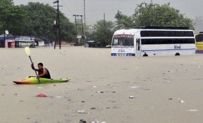A man rows past a bus partly submerged in flood water in Rishikesh, in Uttarakhand on Tuesday...