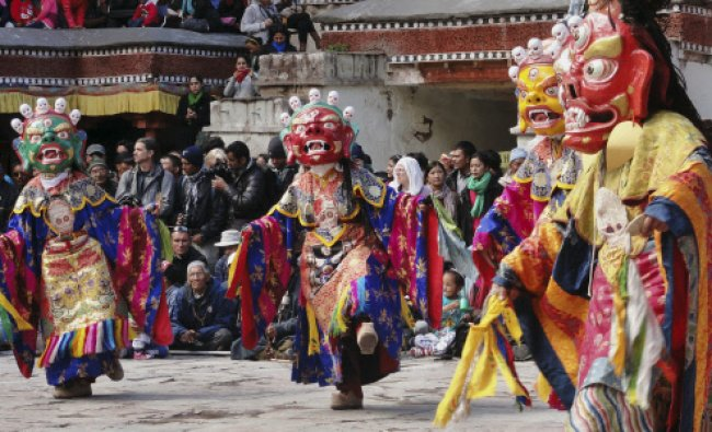 Buddhist monks in traditional attire perform a dance on the first day of the annual festival...
