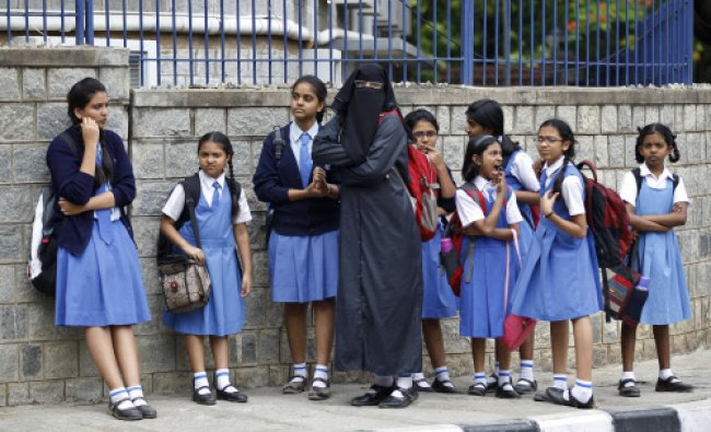 A veiled school girl stands with fellow students at the end of the day outside a school in Bangalore