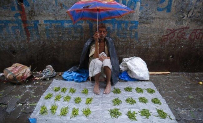 A vegetable vendor sits under an umbrella on a tarpaulin sheet at a market during monsoon rains...