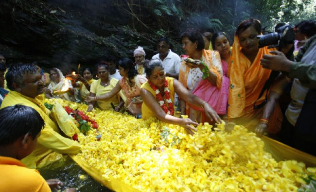 Devotees prepare buttercups placed in a sari as an offering as part of the Ganga Dhaaraa festival...