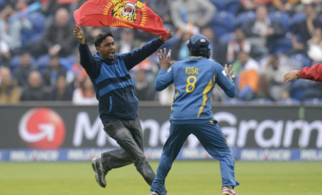 A protester runs towards Sri Lanka\'s Kusal Perera as he carries a Tamil Eelam flag during the ICC...