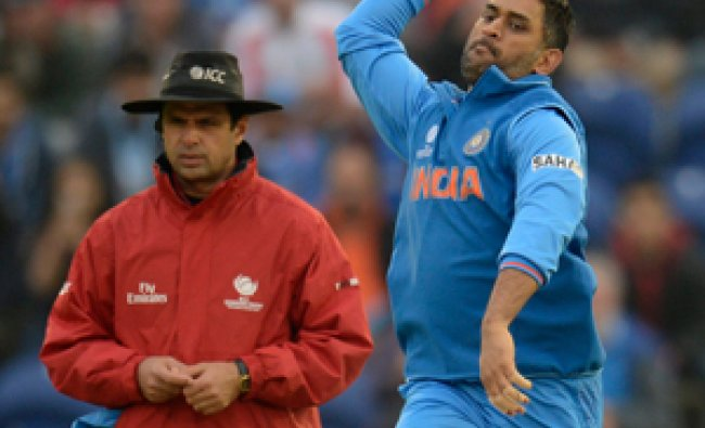 India\'s Mahendra Singh Dhoni bowls as umpire Aleem Dar (L) looks on during the ICC Champions Trophy.