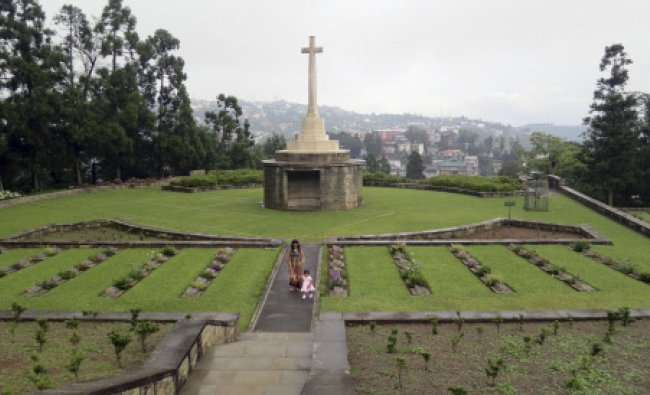 In this Thursday, June 20, 2013 photo, a woman walks after a child at the Kohima War Cemetery...