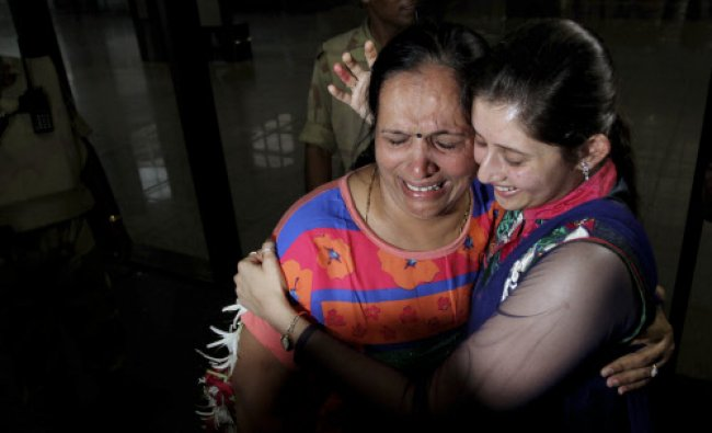 A flood affected pilgrim Sudhaben Bhalala, left, breaks down as she hugs her daughter-in-law...