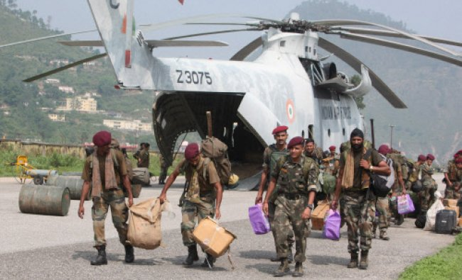 Army men unload relief material from an IAF MI-26 helicopter at Gauchar district Chamoli...