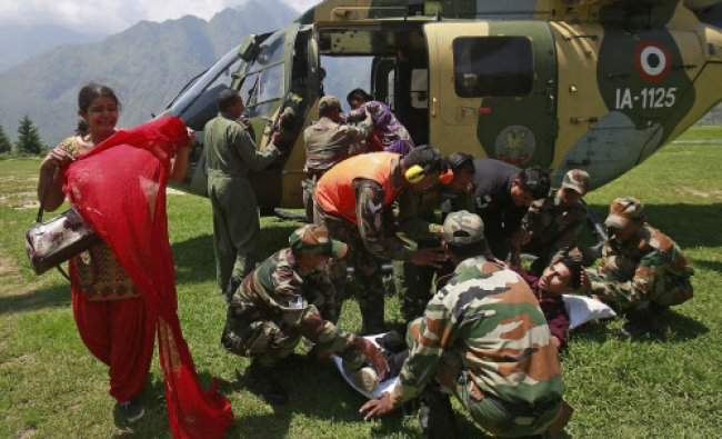 A woman cries as her husband is put on a stretcher by soldiers from an army helicopter, during...
