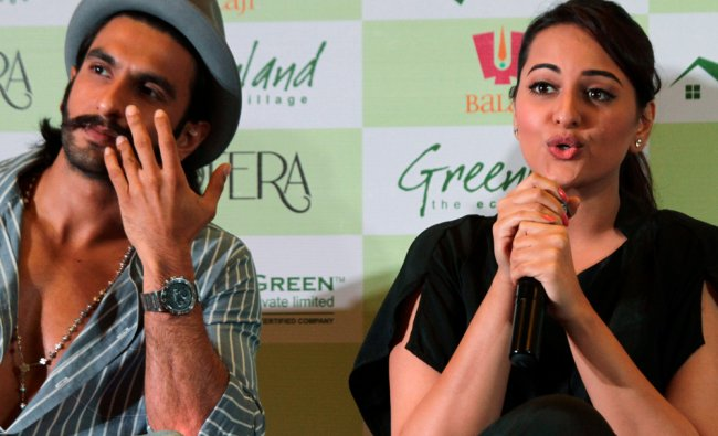 Sonakshi Sinha peaks next to her fellow actor Ranveer Singh during a promotional event of Lootera...