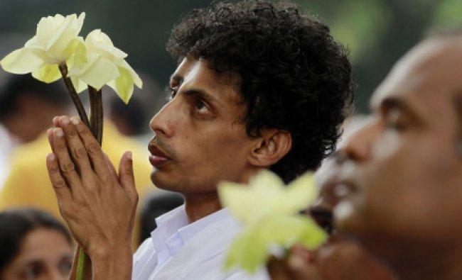 Sri Lankan Buddhist devotees offer prayers during Poson full moon day religious observance at a...